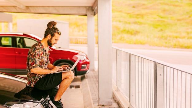 Freelancer sentado en el capó y trabajando de forma remota