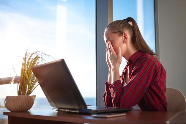 Freelancer siente fatiga visual y masajea los ojos después de un largo día de trabajo