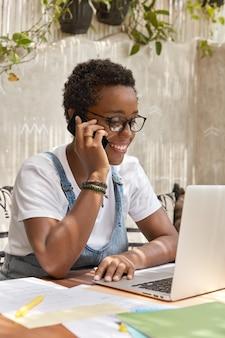 Freelancer sonriente exitoso recibe asesoramiento a través de teléfono celular