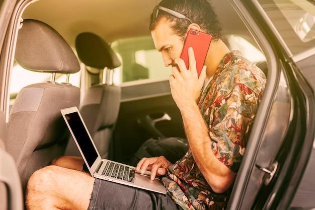 Freelancer trabajando con laptop y smartphone en auto