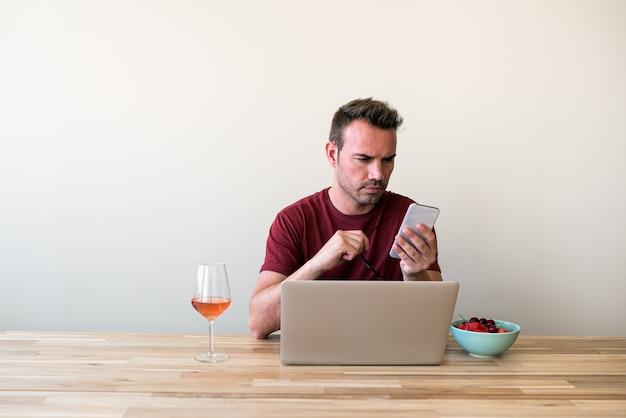 Freelancer usando laptop y teléfono móvil en casa