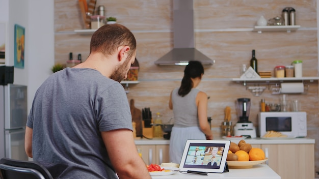 Freelancer durante una videoconferencia en una tableta mientras la esposa está cocinando el desayuno en la cocina. emprendedor disfrutando de una taza de café durante una videoconferencia con compañeros de trabajo.