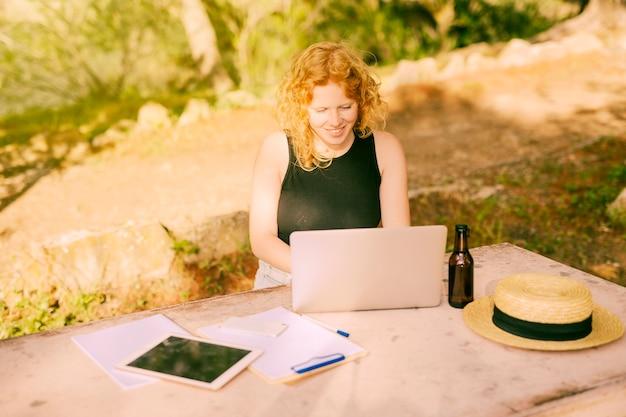 Freelancing femenino joven en el ordenador portátil en el escritorio en naturaleza