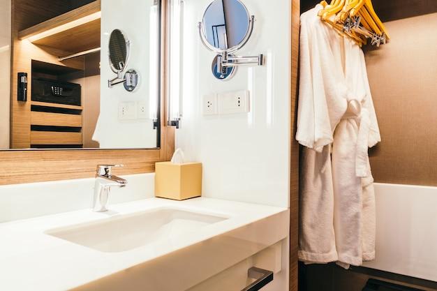 Fregadero blanco y decoración de agua de grifo en baño.