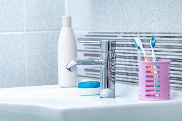 Fregadero, grifo con agua y accesorios de baño para el cuidado de la piel y lavado en el baño de la casa.