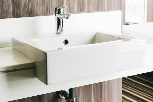 Fregadero y grifo modernos blancos en baño.