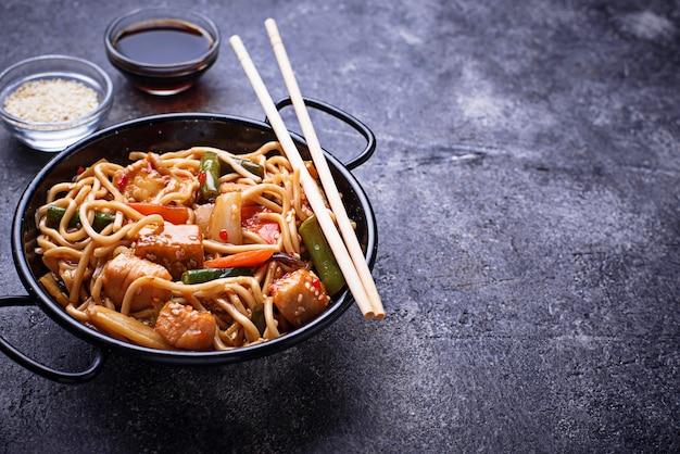 Freír los fideos con pollo, tofu y vegetales.