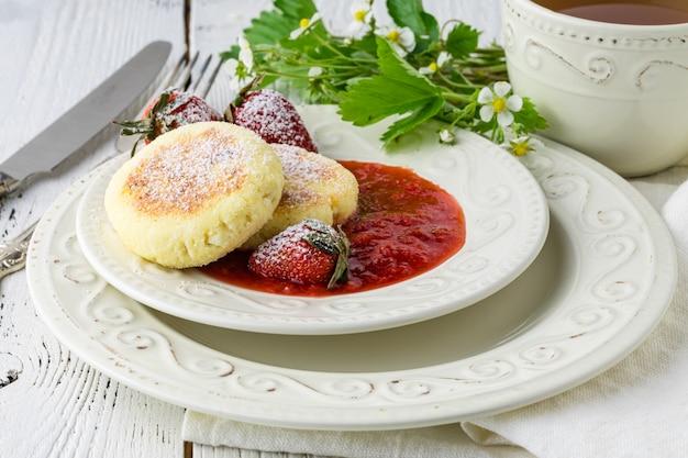 Freír panqueques caseros de requesón syrniki ruso con fresa en placa. hora del desayuno