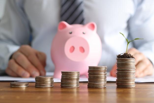 Frente al empresario hay cilindros de monedas y hucha de cerdo rosa