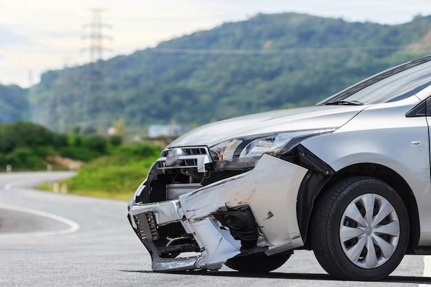 El frente del coche plateado se daña por accidente de choque en la carretera.