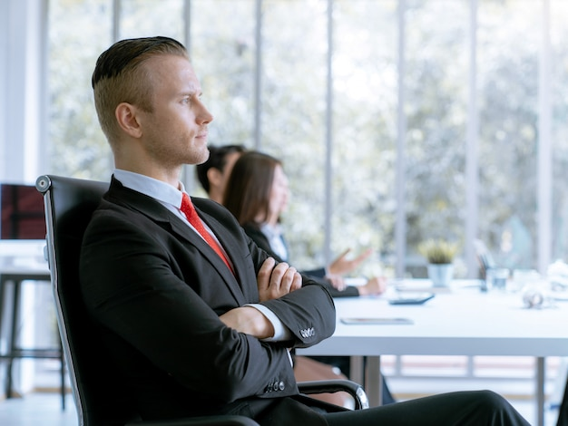 Frente de hombre de negocios europeo elegante del retrato del trabajo en equipo durante la conferencia de la reunión en la oficina de la compañía