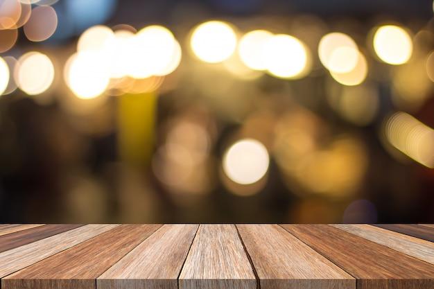 Frente de mesa de madera marrón y cálido fondo borroso