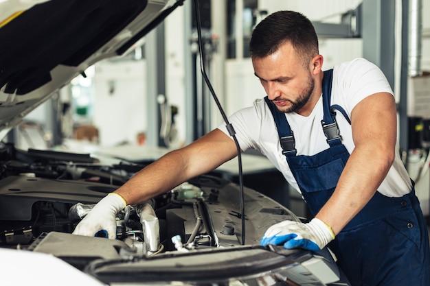 Frente trabajador de vista masculino en el taller de servicio de coche