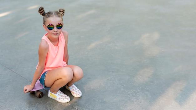 Frente vie de niña sentada en patineta