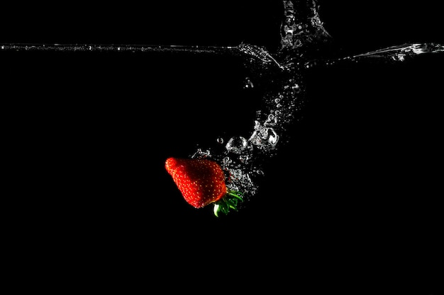 Fresa en agua con fondo negro.