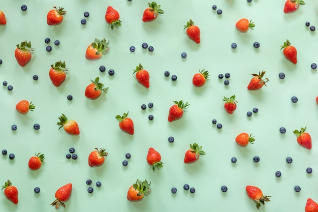 Fresa y arándano sobre fondo verde pastel. vista plana de comida