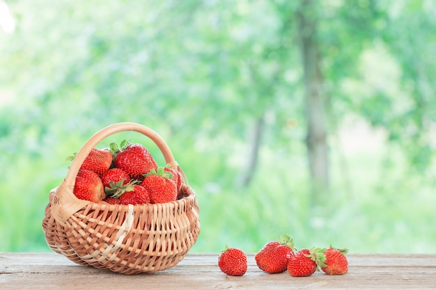 Fresa en cesta en mesa de madera al aire libre