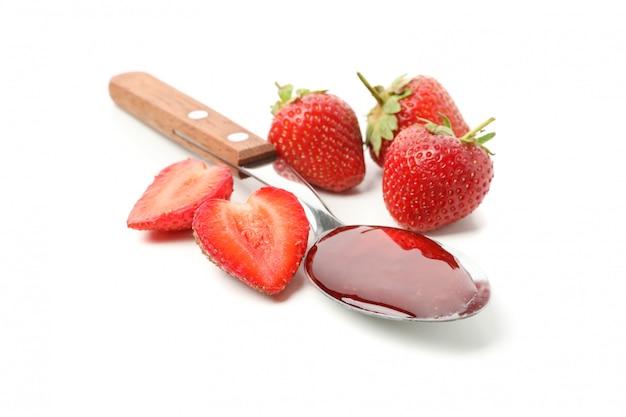 Fresa y cuchara con mermelada de fresa aislado en blanco