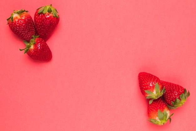 Fresa dulce madura sobre fondo rosado