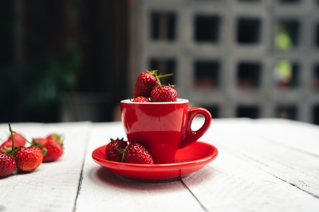 Fresa dulce rojo brillante sobre una mesa blanca