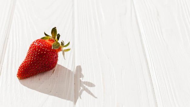 Fresa fresca sobre fondo de madera
