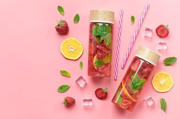 Fresa con infusión de agua, bebida helada de verano con fresa, limón y hojas de menta sobre fondo rosa