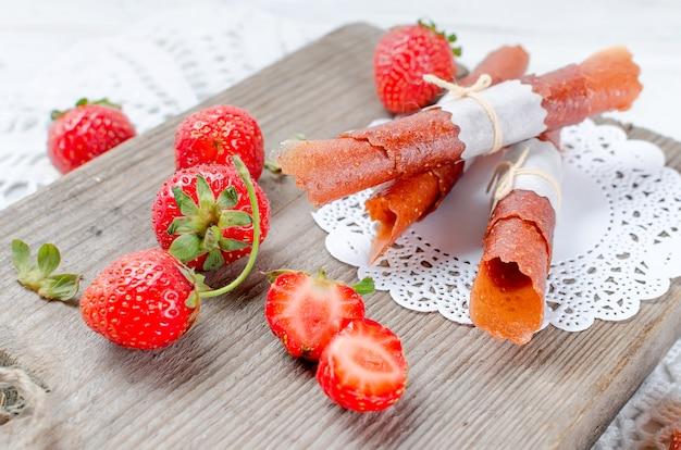 Fresa jugosa madura, papas fritas secas de fruta y pastilla de fresa
