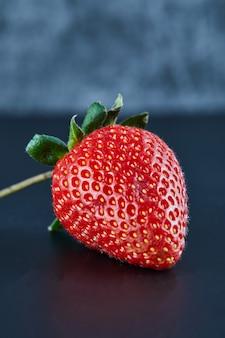 Fresa roja fresca sobre superficie oscura. de cerca