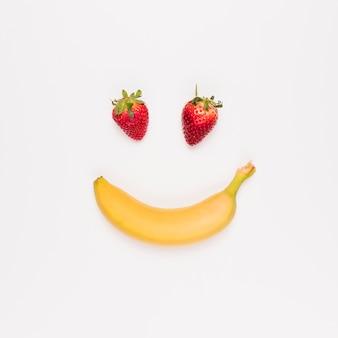 Fresa roja y plátano amarillo sobre fondo blanco