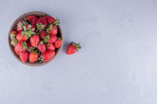 Fresas apiladas en un cuenco de madera sobre fondo de mármol. foto de alta calidad