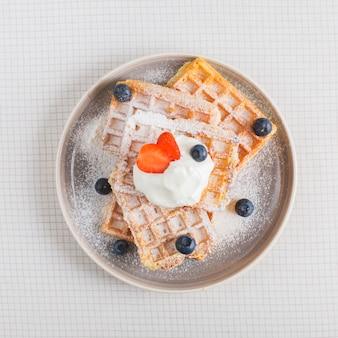 Fresas y arándanos en crema batida sobre la pila de waffles en un plato sobre el fondo a cuadros