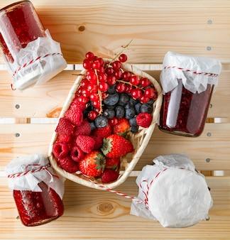 Fresas, arándanos, grosellas rojas y frambuesas en una cesta y frascos de vidrio con mermeladas en la mesa de madera
