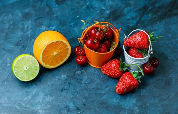 Fresas y cerezas en mini cubos con naranja, lima plana sobre un fondo azul sucio