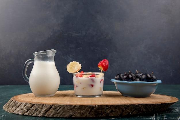 Fresas en crema servidas con leche y cerezas sobre fondo negro