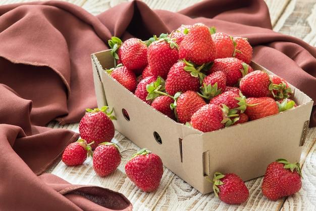 Fresas deliciosas frescas en caja de cartón en mesa de madera blanca