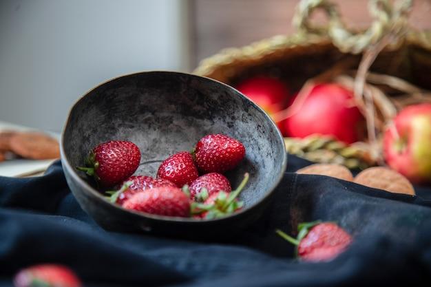 Fresas dentro del tazón de fuente, galletas y cesta de la manzana en una estera negra, cesta borrosa.