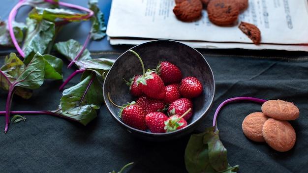 Fresas dentro de un tazón, galletas, un libro y hojas sobre una estera negra.