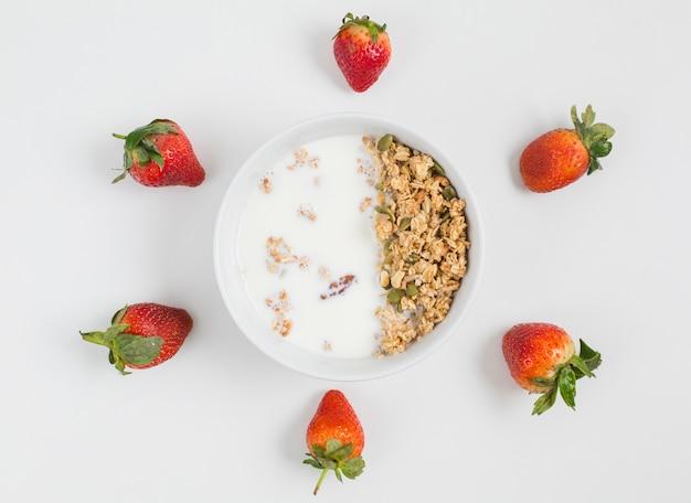 Fresas enteras decoradas con un tazón de avena casera con leche aislada sobre fondo blanco