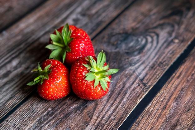 Fresas escocesas rojas frescas en la parte superior de la mesa de madera