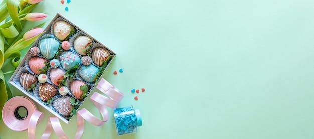 Fresas, flores y decoración hechas a mano cubiertas de chocolate para cocinar postres sobre fondo verde con espacio libre para texto