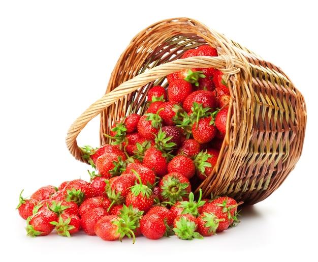 Fresas frescas en una canasta sobre un fondo blanco.