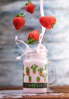 Fresas frescas cayendo en un vaso para hacer un delicioso batido de fresa. pared de madera