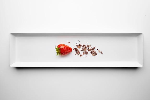 Fresas frescas maduras cerca de las migajas de chocolate presentadas en un plato de cerámica rectangular central en un restaurante que sirve aislado sobre fondo blanco.