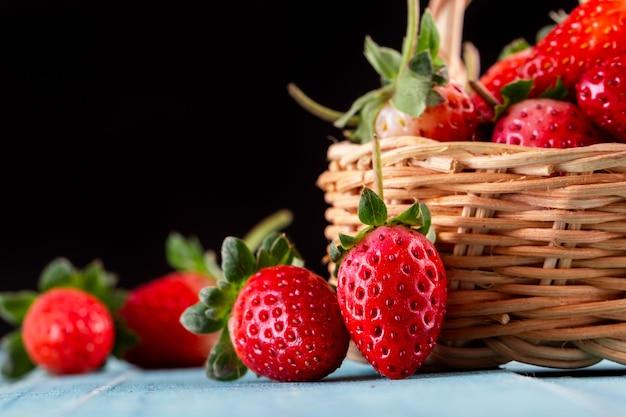 Fresas frescas en un recipiente en la mesa de madera