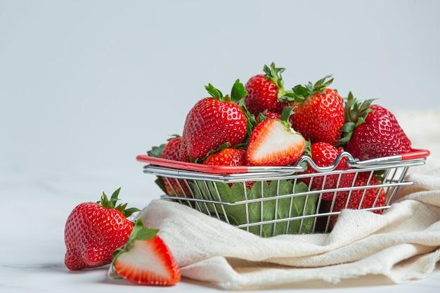 Fresas frescas en un recipiente sobre fondo blanco.