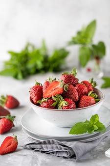Fresas frescas en un recipiente sobre una mesa de hormigón blanco.