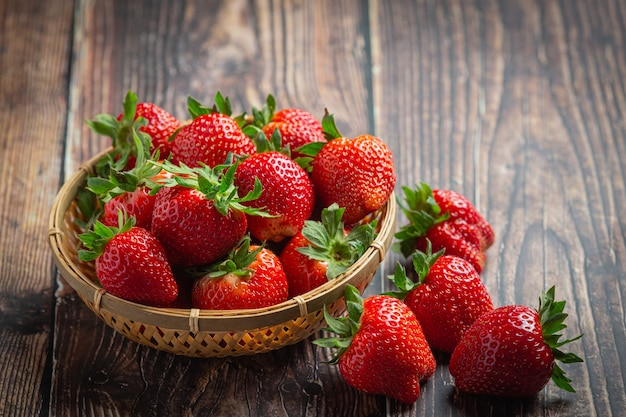 Fresas frescas en un recipiente sobre la mesa de madera