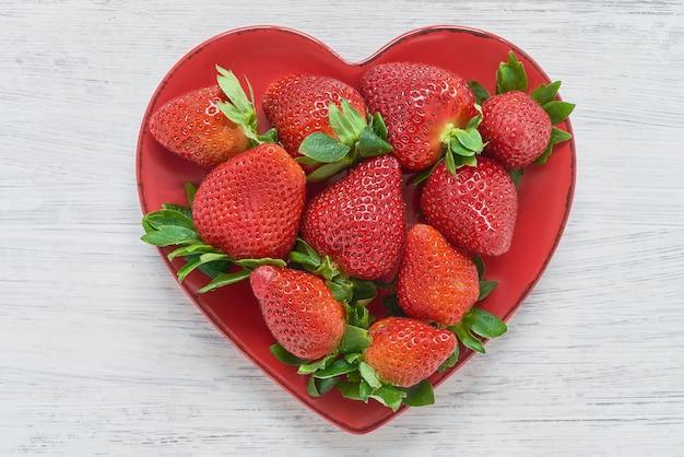 Fresas frescas en un tazón en forma de corazón en la tabla blanca.