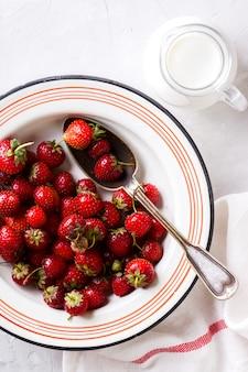 Fresas frescas en el tazón de hierro con leche en jarra de vidrio