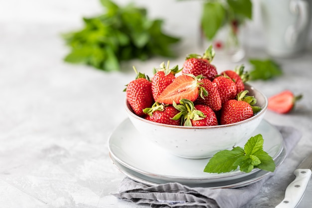 Fresas frescas en un tazón y ramitas de menta en una mesa de hormigón blanco. ingrediente para batidos.